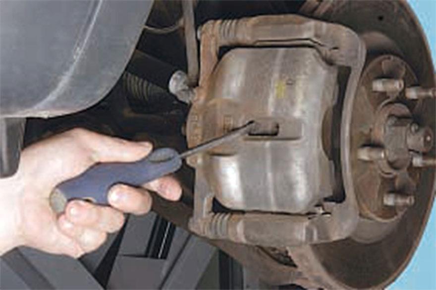 Отвертка с плоским шлицем помещается в зазор, расположенный между колодкой и давящим поршнем