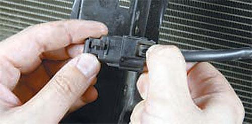 Извлеките фиксатор из отверстия в кронштейне замка капота