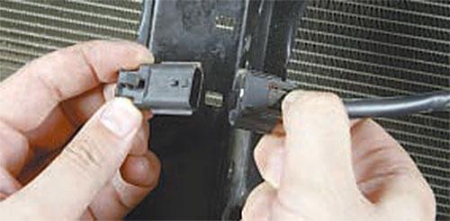 Нажмите на фиксатор колодки жгута проводов датчика             наружной температуры